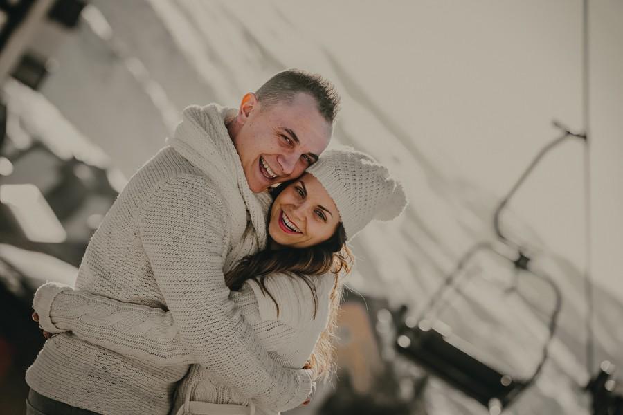 pareja en Sierra Nevada frente un edificio nevado