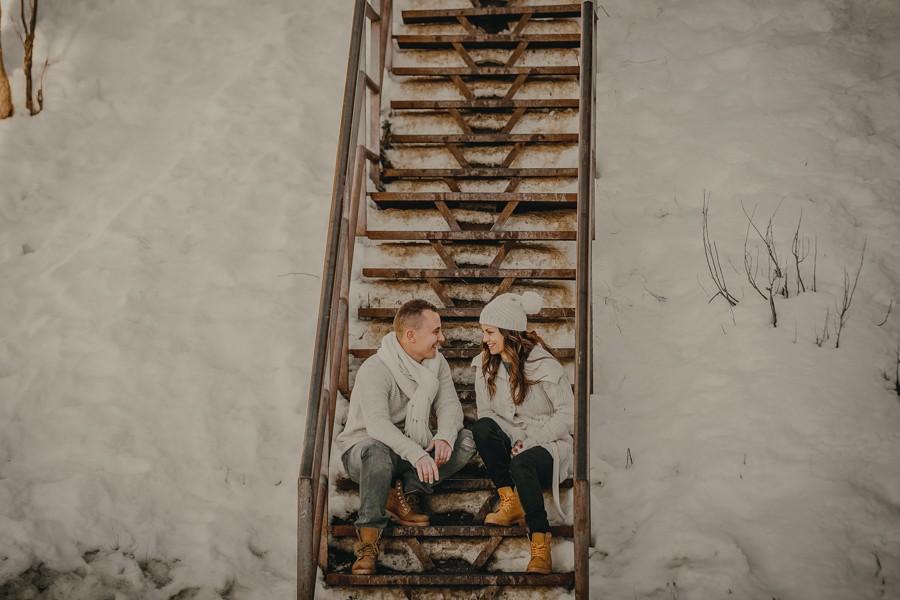 pareja sentada en escaleras rodeada de nieve