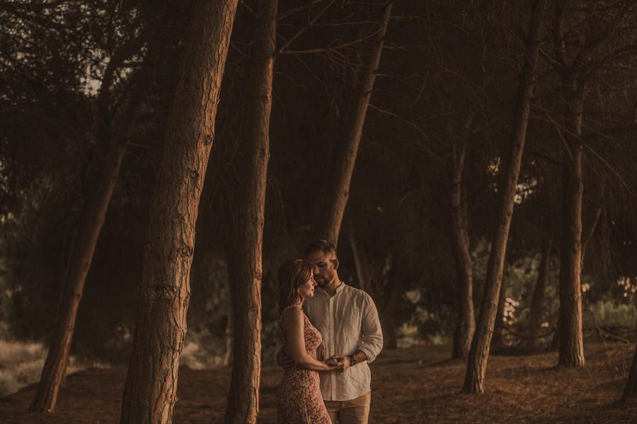 cogidos de la mano se miran , rodeado de árboles con la luz del atardecer