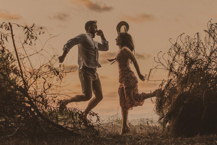 la pareja salta de fondo un rojo atardecer , fotos preboda natural