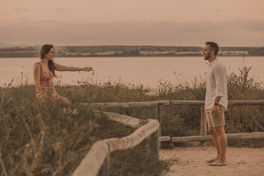Noemi extiende su mano invitando a Manu a acercarse , de fondo , la laguna