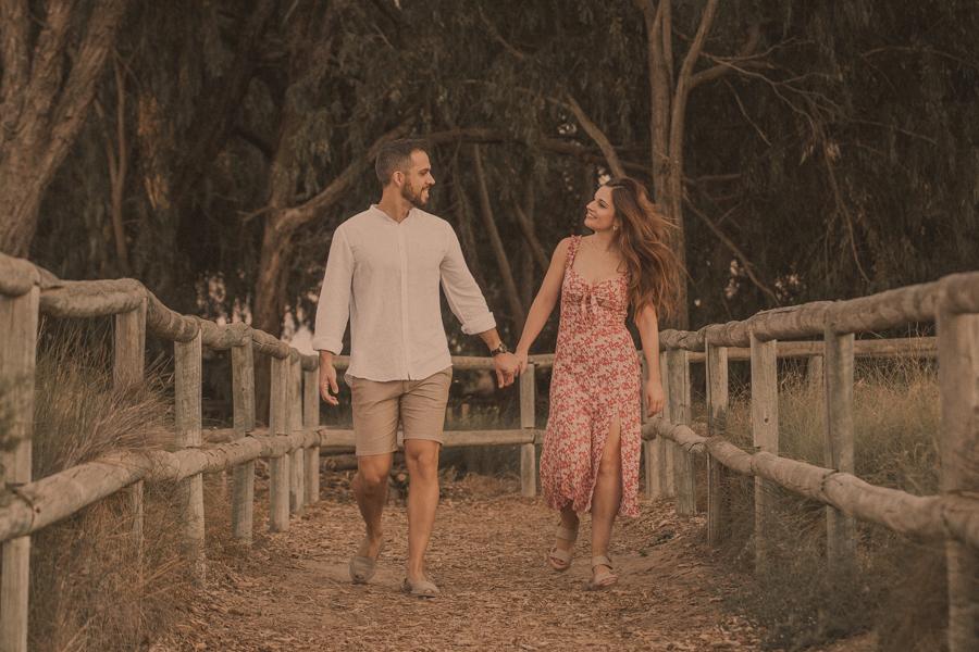 la pareja camina cogidos de la mano por un manto de hojas secas en plena naturaleza