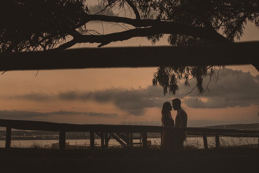 contraluz del atardecer que deja ver la silueta de las ramas de los árboles y de la pareja , uno frente al otro