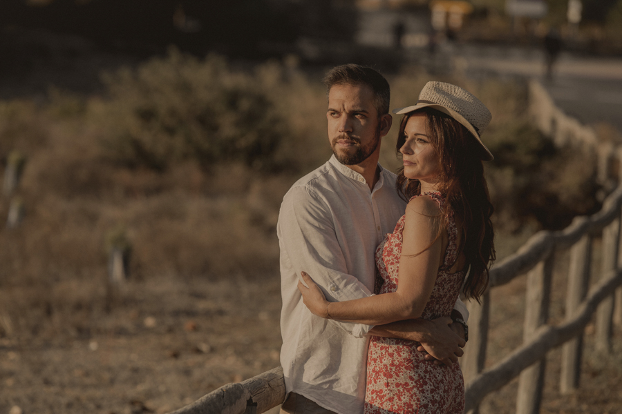 pareja mirando al horizonte, la chica lleva un sombrero, están apoyados en un vallado de madera.