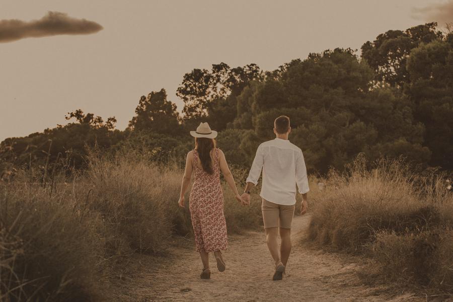 la pareja cogida de la mano camina hasta adentrarse en la naturaleza del parque